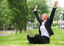 Successful  businesswoman with laptop and arms outstretched Stock Images