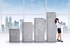 Successful businesswoman leans on bars Stock Image