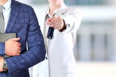 Successful businesswoman offering a car key.Business man holding documents behind Stock Image
