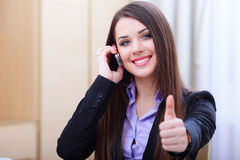 Successful businesswoman on phone. Happy successful businesswoman with cell phone and thumbs up gesture Royalty Free Stock Photos