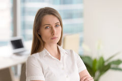 Successful businesswoman ready for challenges. Young serious woman standing in modern office interior with arms crossed. Successful businesswoman ready for royalty free stock photos