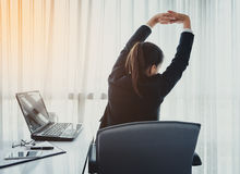 Successful businesswoman relaxing in her chair at the office Stock Photo