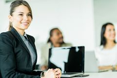 Successful businesswoman sitting at an office desk with colleagu Stock Images