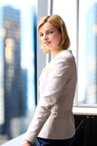 Successful businesswoman standing near with  window. Downtown background behind. Royalty Free Stock Photos