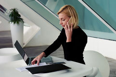 Successful businesswoman talking on mobile phone during preparation for delivery of report Royalty Free Stock Images