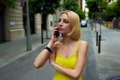 Successful businesswoman talking on smart phone while standing at city street in summer Stock Photo