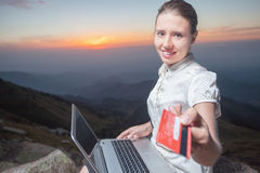 Successful businesswoman on top of mountain, using a laptop Royalty Free Stock Images