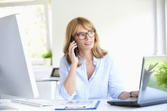Free Successful Businesswoman Using Her Mobile Phone At The Office Royalty Free Stock Photo - 120570905