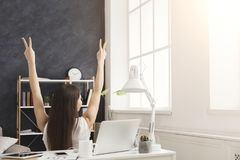 Business woman with raised hands in office, back view. Successful businesswoman wins. Girl with raised hands and victory gestures having rest in office chair Stock Photo
