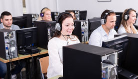 Successful call center. Working process of successful call center team at office and happy operators. Focus on the brunet woman Royalty Free Stock Image