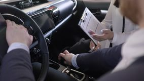 Successful car sale, female auto dealer advises client after hands over keys to customer and shakes hands sitting inside. Cabin close-up at showroom stock video