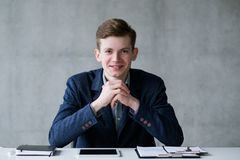 Successful career ambitious young office worker. Successful career. Ambitious office worker. Cheerful young man sitting at desk, smiling. Copy space royalty free stock photo