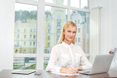 Successful career.The friendly and confident young woman sitting Stock Photo
