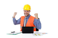 Successful caucasian man architect, clenched fists. Successful attractive caucasian man architect with safety helmet in the office with laptop, clenched fists Royalty Free Stock Photos
