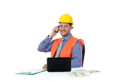 Successful caucasian man architect, talking. Successful attractive caucasian man architect with safety helmet in the office working with laptop and talking by stock photo