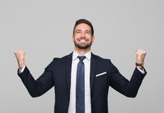Successful caucasian professional businessman winning. Successful young caucasian professional winner businessman on gray background royalty free stock image