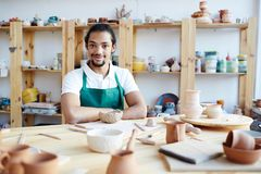 Successful ceramic master at work. Portrait of young mixed race male ceramist sitting at workshop table with handmade pottery and smiling at camera Royalty Free Stock Images