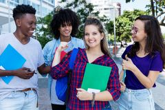 Successful cheering northern european female student with group of friends stock photo