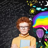 Successful child boy on blackboard background with science and art pattern.  royalty free stock image
