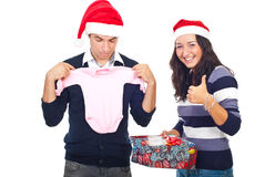 Successful Christmas gift. Woman giving thumbs up and smiling  while her husband being surprised of his Christmas gift isolated on white background Stock Photo