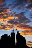 Successful climbing team. Team of climbers conquer the summit of a challenging rock spire Stock Image