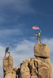 Successful climbing team. Team of male climbers conquer the summit of a challenging rock spire Royalty Free Stock Image