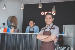 Cafe owner standing with crossed arms. Successful coffee shop owner standing with crossed arms with partner at the background Stock Photos