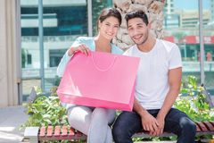 Successful collaborative shopping. Couple sitting on a bench Stock Image
