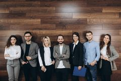 Successful company with happy workers standing in row in modern office royalty free stock photos