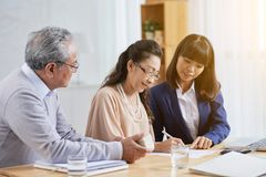 Successful Completion of Meeting with Estate Agent. Working process at boardroom: attractive Asian estate agent showing where to put signature to senior clients Royalty Free Stock Photography