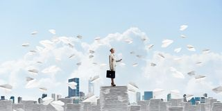 Successful confident business woman in suit. Confident business woman in suit standing among flying paper planes with cloudly skyscape on background. Mixed Royalty Free Stock Photos