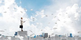 Successful confident business woman in suit. Confident business woman in suit standing among flying paper planes with cloudly skyscape on background. Mixed royalty free illustration
