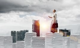 Successful confident business woman in suit. Confident business woman in suit standing on pile of documents with cityscape and sunlight on background. Mixed Stock Photos