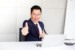 Successful confident businessman ,showing thumbs up or like sitting at office desk,success, good idea, great job business concept.  royalty free stock images