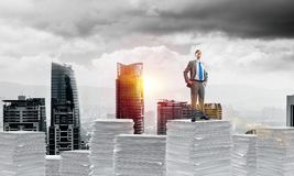 Successful confident businessman in suit. Confident businessman in suit standing on pile of documents with cityscape and sunlight on background. Mixed media stock illustration
