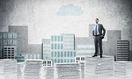 Successful confident businessman in suit. Confident businessman in suit standing on pile of documents with drawn cityscape background. Mixed media royalty free illustration