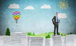 Successful confident businessman in suit. Confident businessman in suit standing on pile of documents with drawn landscape on background. Mixed media vector illustration