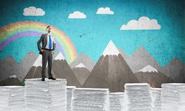 Successful confident businessman in suit. Confident businessman in suit standing on pile of documents with drawn landscape on background. Mixed media stock illustration
