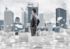 Successful confident businessman in suit. Confident businessman in suit standing on pile of documents among flying paper planes with cityscape on background stock illustration