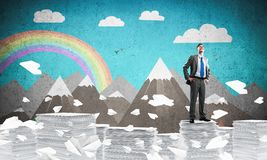 Successful confident businessman in suit. Confident businessman in suit standing on pile of documents among flying paper planes with drawn landscape on royalty free illustration