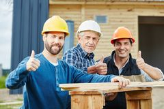 Successful craftsmen holding thumbs up. Successful craftsmen team holding thumbs up as sign of cooperation stock photos