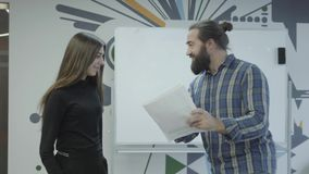 Successful creative bearded boss in casual clothes riding a skate board around the office. The manager is satisfied with. The reports and the work of his stock video
