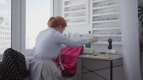 Successful cute red-haired woman sews at the table in workshop. Seamstress works diligently and carefully. Hobby and. Beautiful red-haired woman sews a red skirt stock video footage