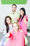 Successful dentist team and happy patient. Showing like gesture royalty free stock photo