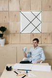 Successful designer having coffe breake. In workplace interior. Man with cup of drink royalty free stock images