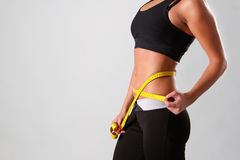 Successful diet. Attractive young girl with measure tape Stock Photography