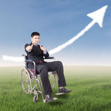 Successful disabled businessman with upward arrow. Portrait of disabled worker showing thumbs up at field while sitting on the wheelchair with upward arrow on Stock Photos