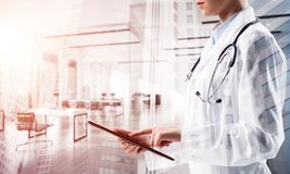 Successful doctor and modern technologies. Confident female doctor in white coat using tablet while standing inside hospital office and modern cityscape view on royalty free stock images