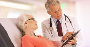 Successful doctor talking with elderly woman patient in the office royalty free stock photo