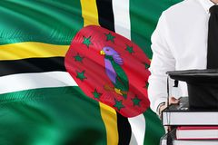 Successful Dominican student education concept. Holding books and graduation cap over Dominica flag background.  stock image